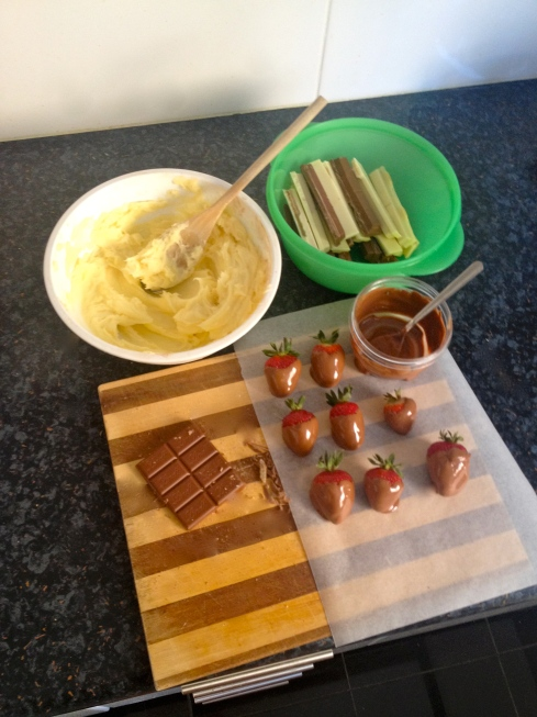 White chocolate icing, White and milk Kit-Kat, chocolate shavings and chocolate dipped strawberries. Would you like some more chocolate with your chocolate cake?
